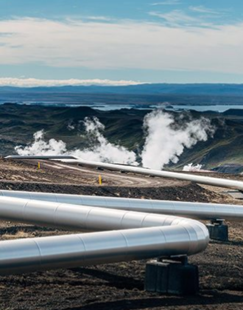 View of a pipeline with steam rising from equipment in the background