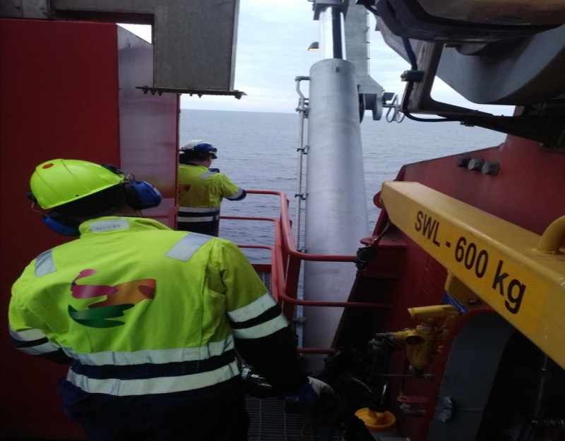 Workers inspecting a crane offshore