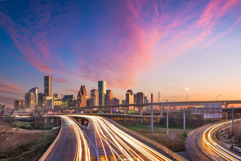 City image at dusk with light trails from cars on roadways