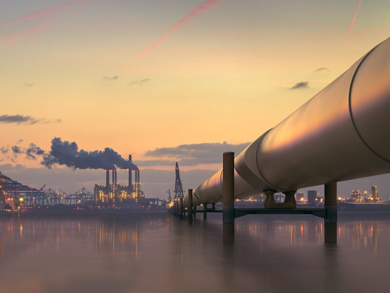 Pipeline across body of water to industrial facility on the far shore