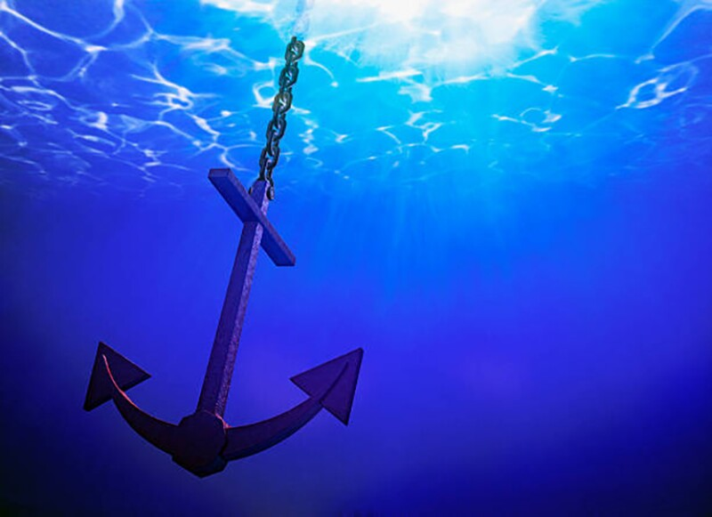Anchor in the water with sun shining from above