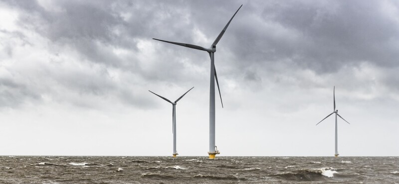 Wind turbines in an offshore wind park during a storm with big waves hitting the shore.
