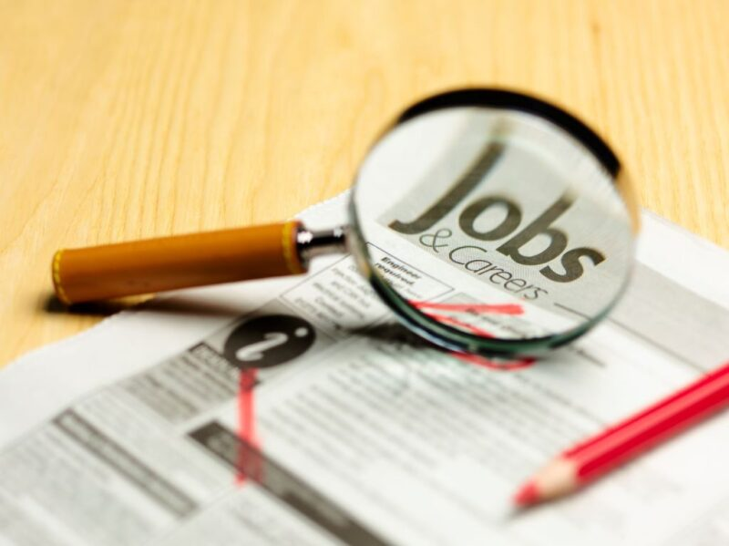 Magnifying glass focused on job ads in newspaper
