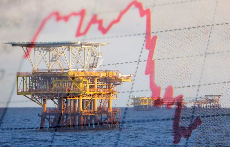 Offshore platforms in background with a graph with red downward trending line superimposed over the top