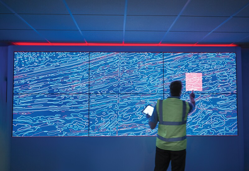 Geologist studying graphical display of oil and gas bearing rock on screens