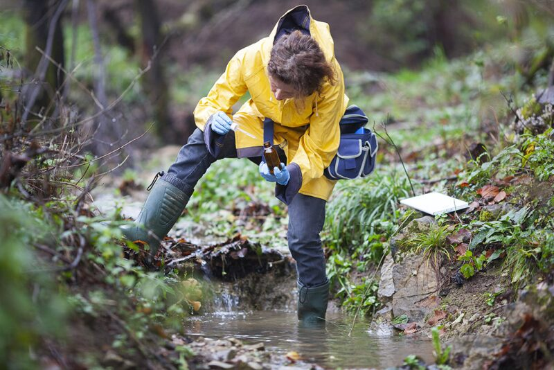 Worker testing water in a stream