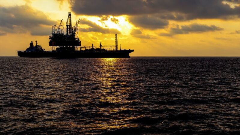 FPSO silhouetted against dramatic sky