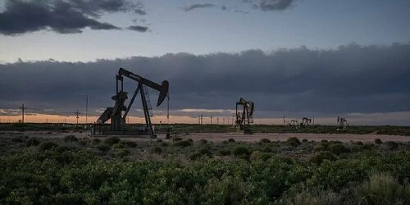 Row of pump jacks with storm clouds in the backgroung