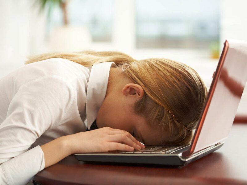 Woman sleeping face down on her laptop