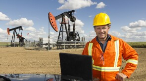 Oilfield professional in front of a rig.