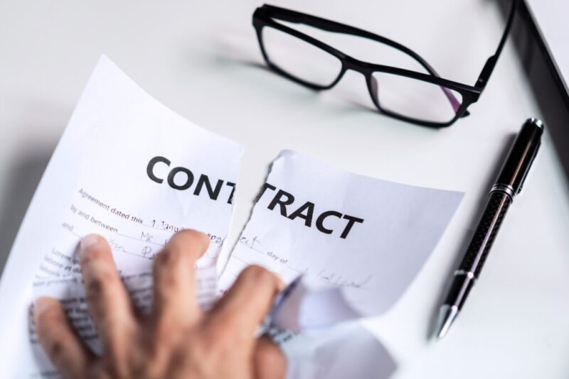 Hand crumpling contract with glasses and pen nearby