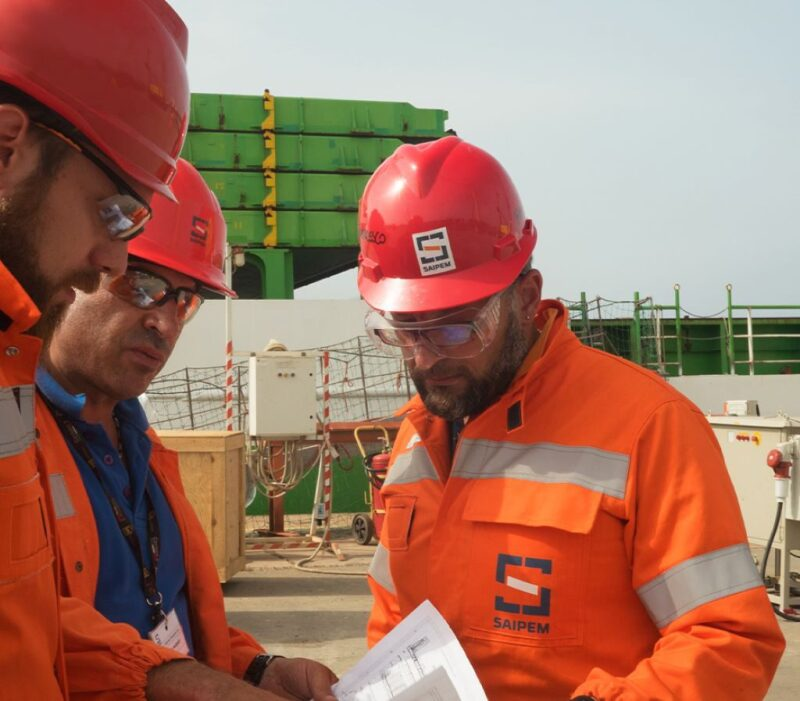 Saipem workers examining documents