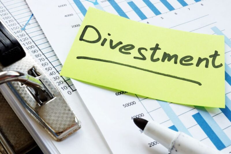 """Word """"divestment"""" written on a post-it note laying on a series of charts"""