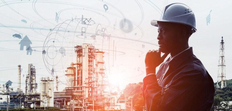 Worker in hard hat in foreground with industrial facilities in background with an overlay of technical/digital symbols