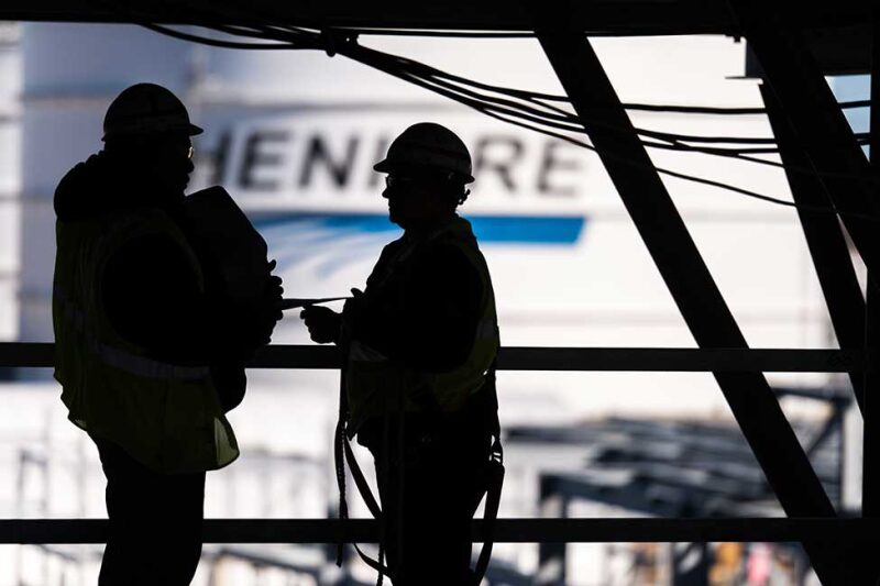 Workers silhouetted against a storage tank with the Cheniere logo