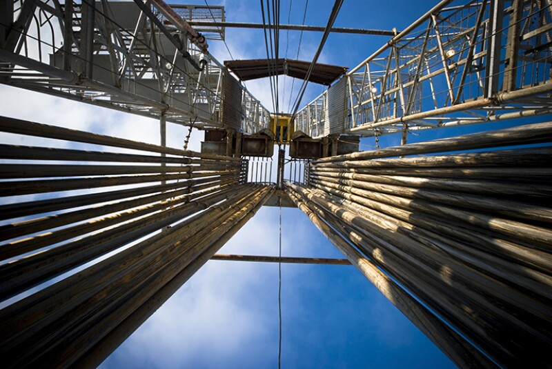 View looking upward at a drilling rig with a full loaded pipe rack