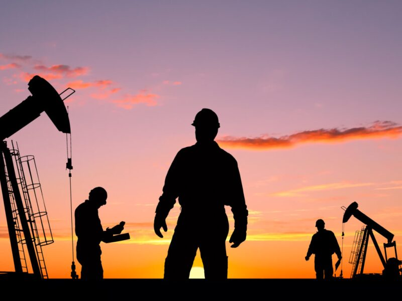 Workers and pumpjacks in silhouette against a sunset sky